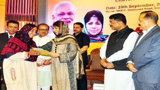 Chief Minister Mehbooba Mufti handing over free LPG connection to a woman at Srinagar in presence of Union and State Ministers on Wednesday.