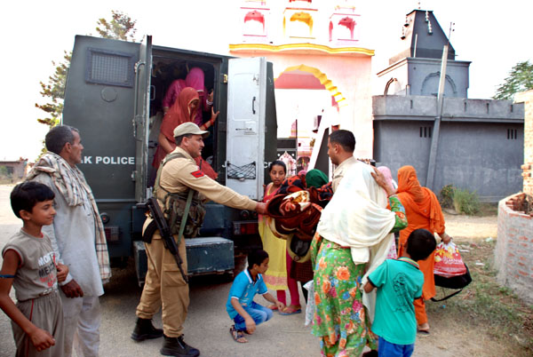 Security personnel shift border villagers in a bullet-proof bunker from Bobiya in Hiranagar sector on Friday.