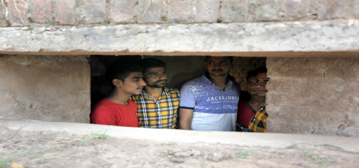 People taking shelter in a bunker at Abdullian in R S Pura sector during sheeling on Tuesday.  —Excelsior/Rakesh