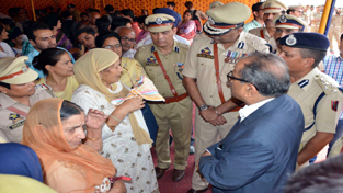 DyCM Dr Nirmal Singh and IGP Jammu Danish Rana interacting with family members of Police martyrs on Friday.