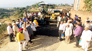 MLA Udhampur Pawan Gupta kick starting work of black topping on Thursday.