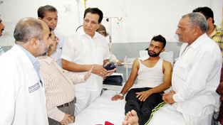 Former Minister R S Chib talking to an injured at GMC Hospital on Thursday.