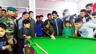 An Army officer aiming at target during a Billiard game in Chinar 9 Jawan Club at Magam.