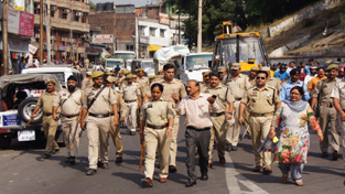 Police escorting JMC officials during anti encroachment drive in Jammu on Friday.