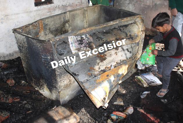 School children examine partially-burnt books among the debris of burnt school building at Goripora Noorbagh Srinagar.Excelsior\Shakeel-ul-Rehman