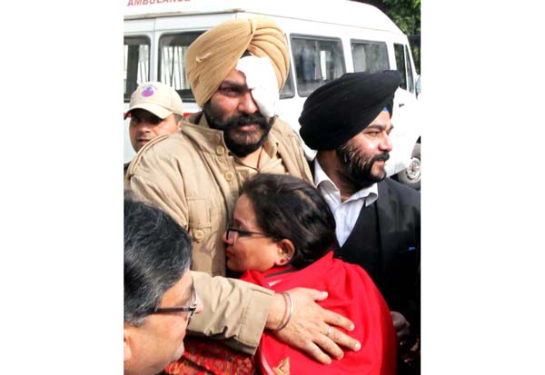 An official injured in Samba encounter hugs his kin outside the GMC Jammu on Tuesday. -Excelsior/Rakesh
