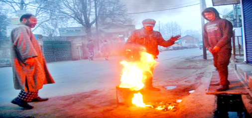 People warming themselves at a bonfire in Srinagar on Tuesday as the minimum temperature dipped to minus 5.5 degree celsius. (UNI)