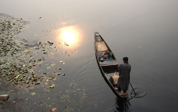 A fisherman rows his boat on Dal lake as temperature shows improvement in Srinagar on Sunday. — Excelsior/Shakeel