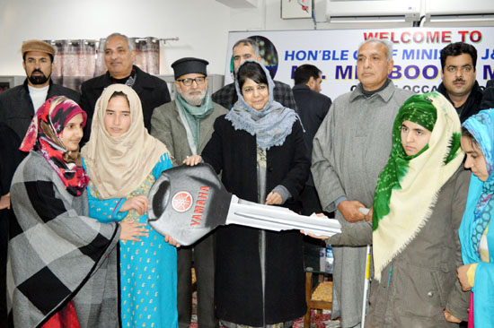 Chief Minister Mehbooba Mufti distributes scooty keys among girl students at Women's Degree College in Pulwama on Monday. -Excelsior/Younis Khaliq