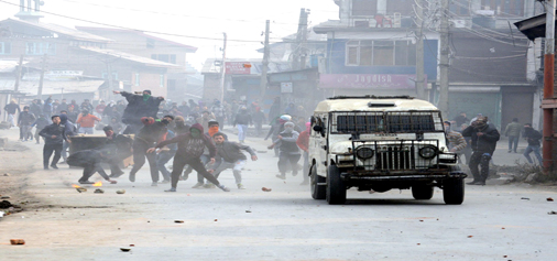 Youths chasing security vehicle during protests at Batamaloo area in Srinagar on Friday. (UNI)