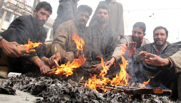 People warming themselves with fire as cold grips Srinagar on Saturday. -Excelsior/Shakeel