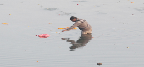 A boy searches recyclable material in Tawi river in Jammu. -Excelsior/Rakesh