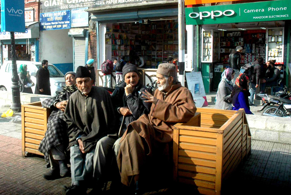 Elders day out in historic Lal Chowk sitting on a bench basking in the Sun as the weather turned pleasant in Srinagar on Sunday. (UNI)