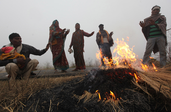 People warming themselves in a field in Jammu on Monday. — Excelsior/Rakesh