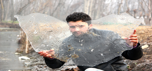 A boy shows a piece of frozen ice on the banks of Dal lake in Srinagar on Monday. —Excelsior/Shakeel