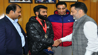 Ace Wushu player Bhanu Pratap Singh alongwith his coach and other dignitaries being honoured by Minister for Sports, Molvi Imran Raza Ansari in Jammu.