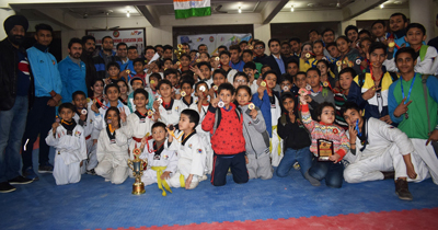 Winners of District Taekwondo Championship posing for a group photograph during concluding ceremony.