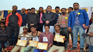 Minister of State for Sports and Transport, Sunil Sharma posing with qualifying athletes at Chowgan ground, Kishtwar on Monday.