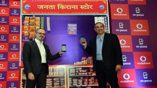 Vodafone Executives displaying M-Pesa PAY solution for merchants and customers.