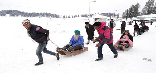 Tourists enjoy sledge riding in Gulmarg on Sunday.  —Excelsior/Shakeel