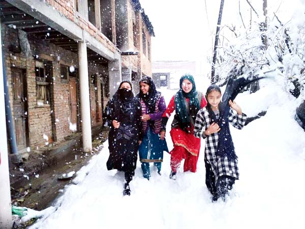 Girls moving through a lane as Bhaderwah town experienced heavy snowfall of season on Monday. -Excelsior/Tilak Raj