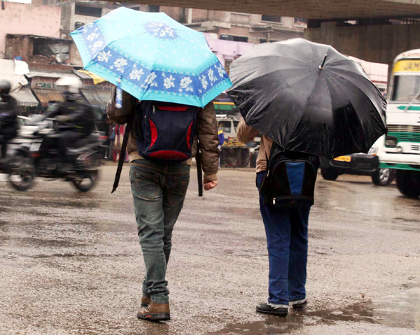 Braving heavy rain, two men with umbrellas moving through a road in Jammu on Wednesday. —Excelsior/Rakesh