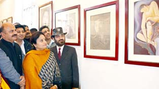 Minister of State for Culture and Tourism Priya Sethi looking at art work during an exhibition.