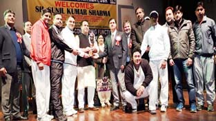 Players of Senior Police XI team posing for a photograph while receiving trophy from Minister of State for Transport and Sports, Sunil Kumar Sharma at Police Auditorium in Jammu on Sunday.