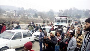 Villagers block National Highway in Udhampur on Tuesday.