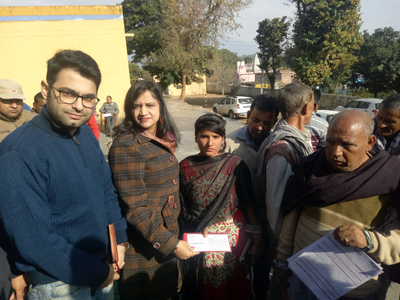 SDM Akhnoor, Sunaina Sharma presenting bank passbooks and ATMs to people during a camp at Akhnoor.