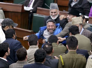 Congress MLA from Kargil Haji Asgar Ali Karbalaie being marshaled out in the Assembly as other MLAs try to protect him on Wednesday. —Excelsior/Rakesh