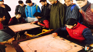Players in action during a match of District Anantnag Carrom Tournament on Monday.