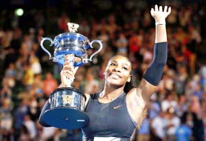 Serena Williams of the US holds her trophy after winning Women's singles final match against her sister Venus Williams during Australian Open at Melbourne.