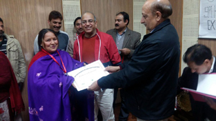 A dignitary presenting certificate to a woman on the concluding day of the special handloom expo at Katra.