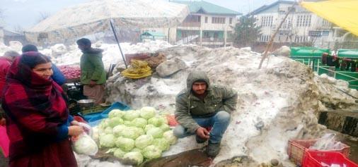 Vendors selling vegetables on snow in Bhaderwah on Saturday. (UNI)