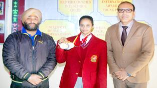 Ace Gymnast Bavleen Kour posing alongwith KC Public School Principal, Amrendra Kumar Mishra and coach on Thursday.