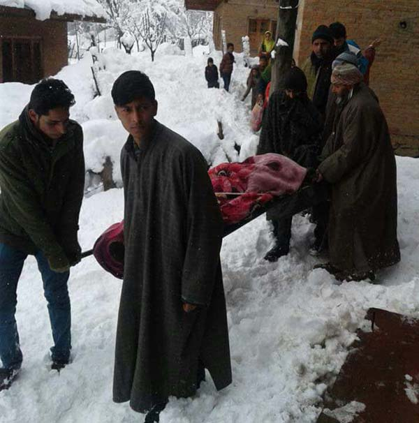 The pregnant woman being carried to hospital through snow clad route in Rafiabad on Saturday.