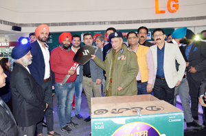 DGP Dr S P Vaid and others presenting key of car to first prize winner of 'Shopping Festival' at Wave Mall on Friday.