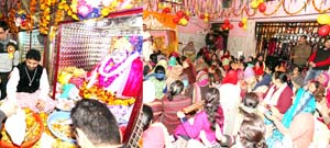 Devotees paying obeisance to Baba Lal Ji (Left) and women performing Satsang (Right) at Baba Lal Ji Temple, Jain Bazaar in Jammu. -Excelsior/Rakesh