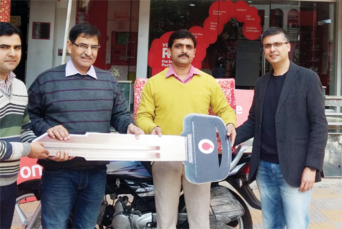 Pawan Sharma of Jammu, the winner of Big Win Season 16 of Vodafone receiving Motor Cycle key from Vodafone officials at Jammu.