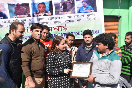 DDC Samba Sheetal Nanda presenting certificate of appreciation to a resident of Kartholi village.
