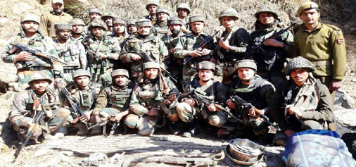 Security personnel pose with arms and ammunition recovered at Bonjwah, Kishtwar on Friday.