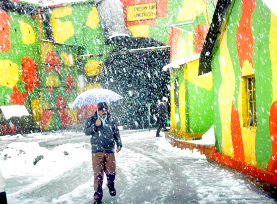A Beacon official covers himself under an umberalla to escape snowfall at Jawahar Tunnel on Srinagar-Jammu National Highway on Tuesday. (UNI).