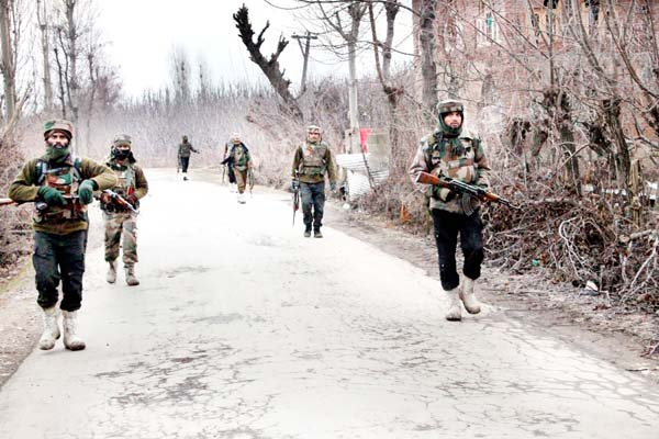 Troops take positions during encounter at Chitragam in Shopian on Thursday. -Excelsior/Younis Khaliq
