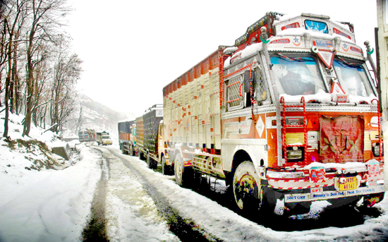 A fleet of trucks loaded with essentials, stranded on the snow bound Zig Road on Srinagar-Jammu National Highway, awaiting clearance of the road to move forward, on Tuesday. (UNI)