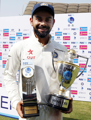 India captain Virat Kohli poses with the Man of the Match and Winners' trophies on Monday.