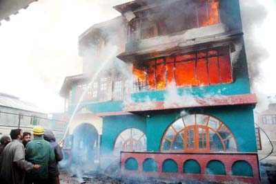 Fire fighters spraying water to control the flames as a major fire broke out in the building of Royal Rattan Palace at Mehjoor Nagar area in Srinagar on Tuesday.