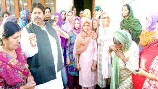 Cong leader Raman Bhalla listening grievances of public at Barjala in Gandhinagar on Sunday.