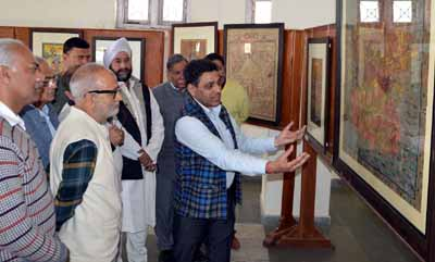 Minister of Public Works Naeem Akhtar looking at the art work on display at Kala Kendra on Saturday.