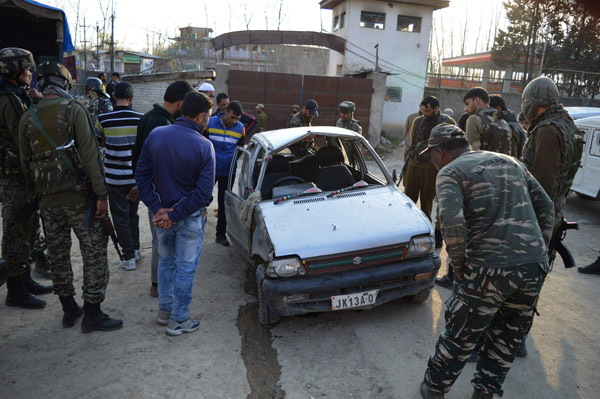 Security personnel examine the car used by the militants at Awantipora on Sunday. —  Excelsior/Younis Khaliq